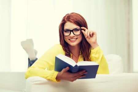 leasure: leasure and home concept - smiling teenage girl in eyeglasses reading book and sitting on couch at home
