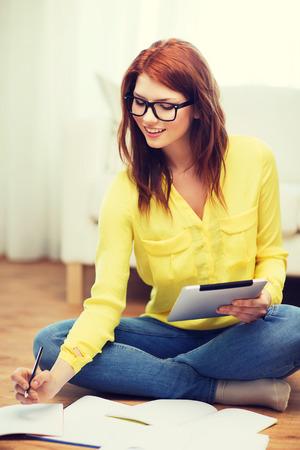 Wirtschaft, Bildung und Technologiekonzept - Lächeln Schülerin in Brillen mit Notebooks und Tablet-PC-Computer zu Hause