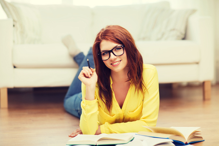 education and home concept - smiling student girl in eyeglasses reading books at home photo