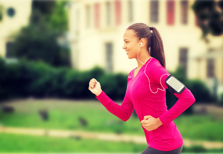 black train: sport, fitness, health, technology and people concept - smiling young african american woman running with smartphone and earphones outdoors