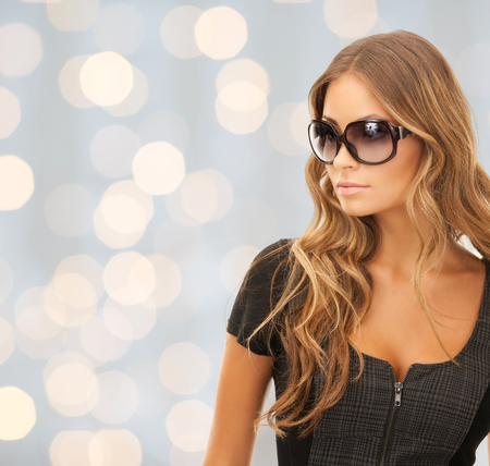 people, fashion, elegance and style concept - beautiful young woman in shades over holidays lights background photo