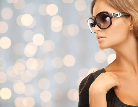 people, fashion, elegance and style concept - close up of beautiful young woman in shades over holidays lights background photo