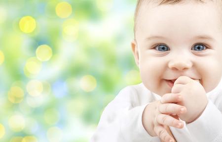 baby s: kinderen, mensen, kinderschoenen en leeftijd concept - mooie gelukkige baby over groene achtergrond verlichting Stockfoto