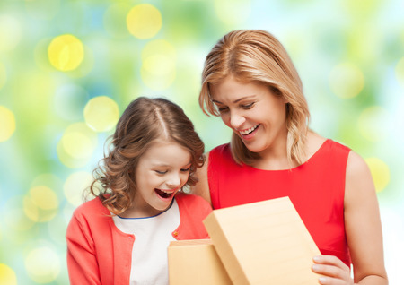 birthday gift: people, holidays, christmas and family concept - happy mother and daughter opening gift box over green lights background