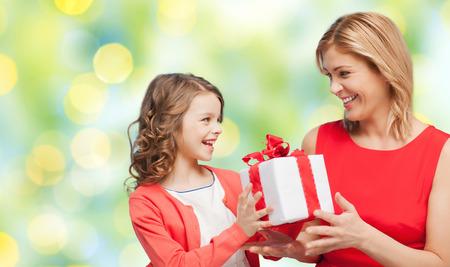 mensen, vakantie, kerstmis en familie concept - gelukkige moeder en dochter het geven en ontvangen gift box over groene achtergrond verlichting