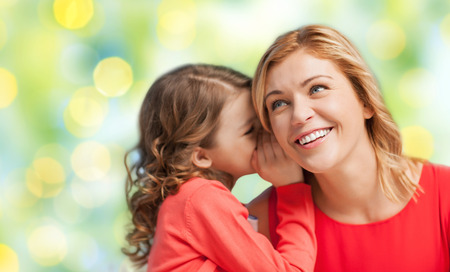 mother and teen daughter: people, trust, love, family and motherhood concept - happy daughter whispering gossip to her mother over green lights background Stock Photo