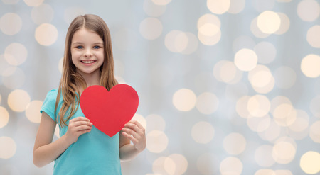 charities: love, charity, holidays, children and people concept - smiling little girl with red heart over lights background Stock Photo