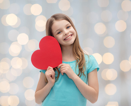 love, charity, holidays, children and people concept - smiling little girl with red heart over lights background Standard-Bild