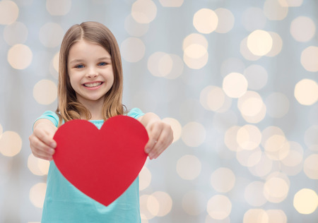love, charity, holidays, children and people concept - smiling little girl with red heart over lights background Фото со стока