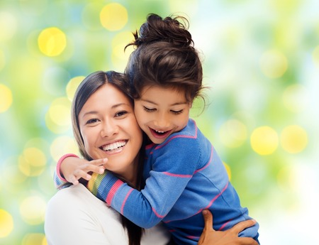 people, happiness, love, family and motherhood concept - happy mother and daughter hugging over green lights background