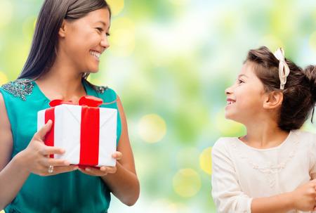 padres hablando con hijos: gente, fiestas, la navidad y concepto de familia feliz - Madre e hija con caja de regalo sobre luces de fondo verde