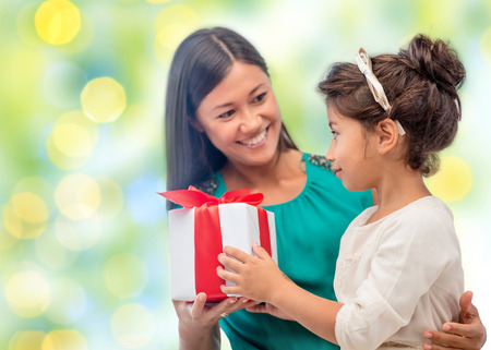 people, holidays, christmas and family concept - happy mother and daughter giving and receiving gift box over holiday green lights background