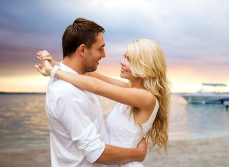 summer holidays, people, love, travel and dating concept - happy couple hugging over sunset beach background photo