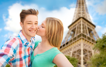 travel, tourism, summer vacation, technology and love concept - happy couple taking selfie with smartphone or camera and kissing over eiffel tower and sky background photo