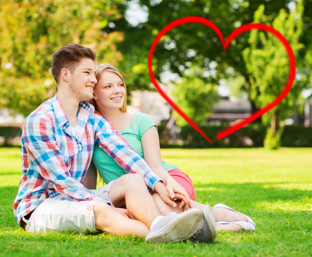 holiday, valentines day, dating and love concept - happy couple sitting on grass in summer park with red heart shape photo