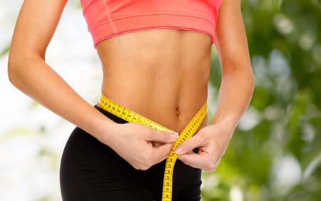 cintura perfecta: dieta, deporte, fitness y la salud concepto - cerca de las manos femeninas medir la cintura con cinta m�trica Foto de archivo