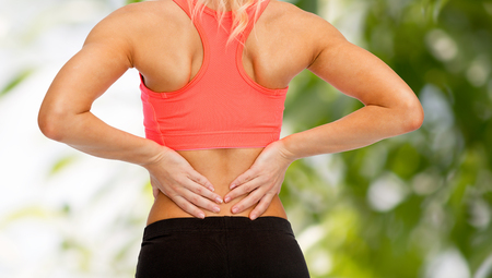 sport injury: fitness, healthcare and medicine concept - close up of sporty woman touching her back