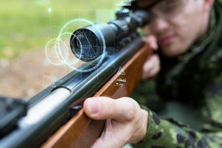 job hunting: hunting, war, army, technology and people concept - close up of young soldier or sniper holding gun with virtual screen projection and aiming in forest