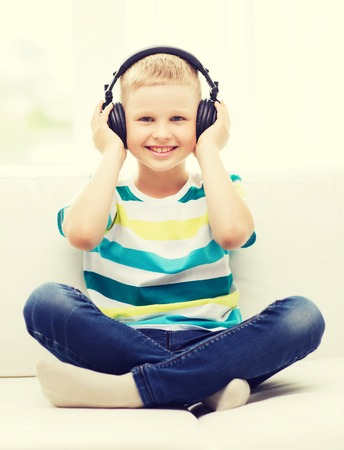 dj boy: home, leisure, new technology, childhood and music concept - smiling little boy with headphones at home
