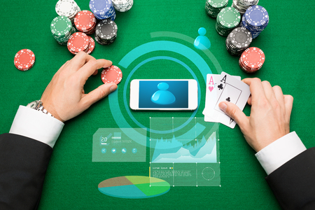 hold em: casino, online gambling, technology and people concept - close up of poker player with playing cards, smartphone and chips at green casino table