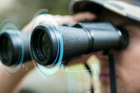 observing: hunting, war, army and people concept - close up of young soldier looking to binocular with virtual hologram and observing forest Stock Photo