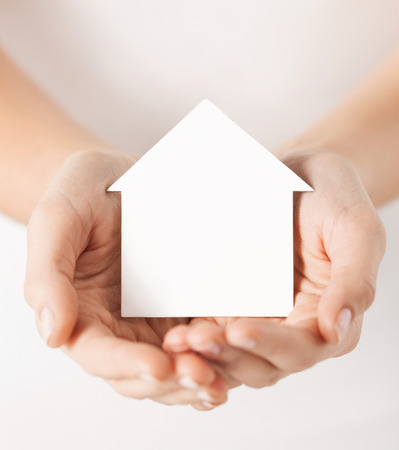 accommodation space: real estate and family home concept - closeup picture of female hands holding white blank paper house