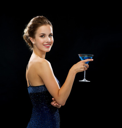 party, drinks, holidays, luxury and celebration concept - smiling woman in evening dress holding cocktail over black background photo