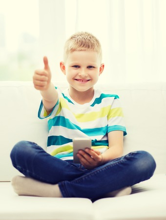 approvement: home, leisure, childhood, technology and internet concept - little boy with smartphone showing thumbs up at home