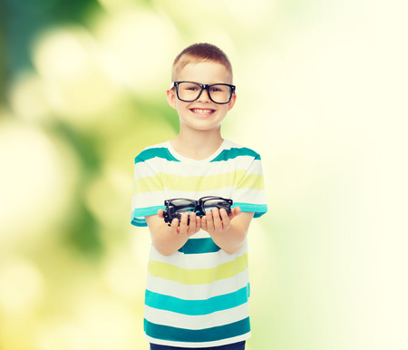 eye exam: vision, health, ecology and people concept - smiling little boy in eyeglasses holding spectacles over green background Stock Photo