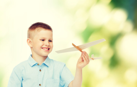 dreams, future, hobby, ecology and childhood concept - smiling little boy holding wooden airplane model in his hand over green background photo