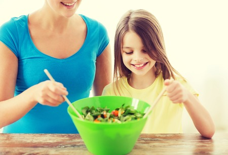 mother and teen daughter: family, child, cooking and home concept - smiling little girl with mother mixing salad in the kitchen Stock Photo