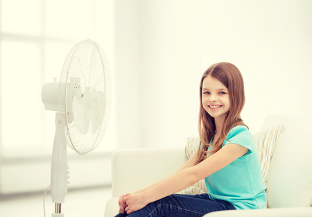 ventilator: summer, weather and equipment concept - smiling little girl sitting on sofa with big fan at home