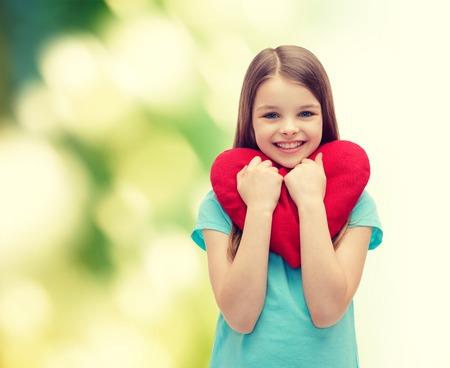 赤のハートを持つ少女の笑みを浮かべて - 愛、幸福と人々 の概念 写真素材