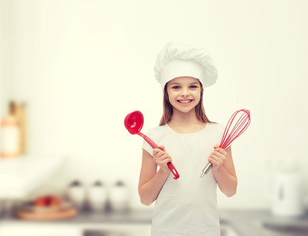 home cooking: cooking and people concept - smiling little girl in cook hat with ladle and whisk