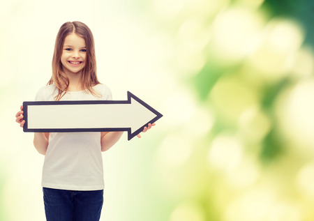 right ideas: advertising and child concept - smiling little girl with blank arrow pointing right Stock Photo