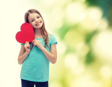 smiling teenagers: love, happiness and people concept - smiling little girl with red heart