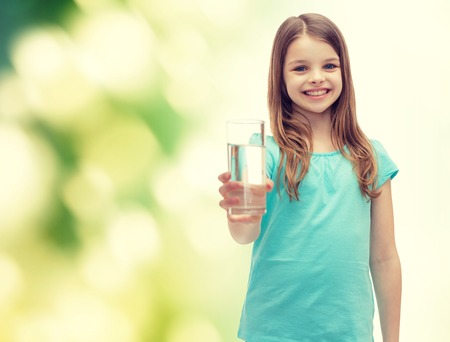 health and beauty concept - smiling little girl giving glass of water Foto de archivo