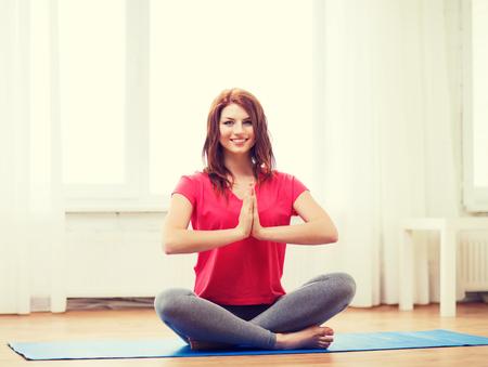 buena postura: aptitud, el hogar y el concepto de dieta - sonriente adolescente pelirroja meditando en casa Foto de archivo