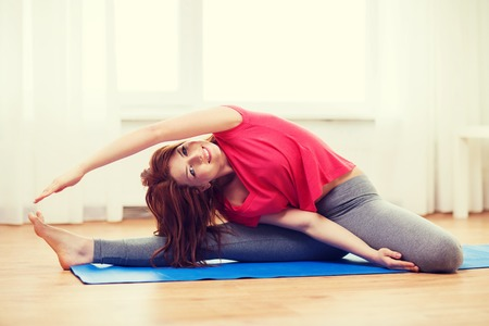 moves: fitness, home and diet concept - smiling teenage girl streching on floor at home