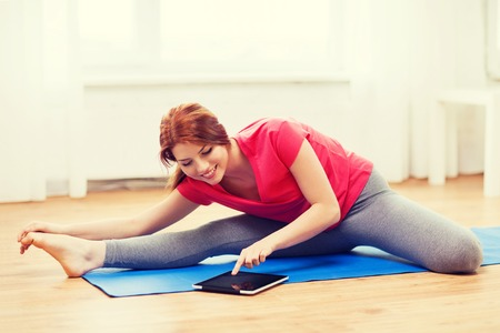 shaping: fitness, home, technology and diet concept - smiling teenage girl streching on floor with tablet pc computer at home