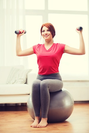 fitness, home and diet concept - smiling redhead girl\ exercising with fitness ball and dumbbells at home