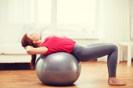 redhead girl: fitness, home and diet concept - smiling redhead girl exercising with fitness ball at home