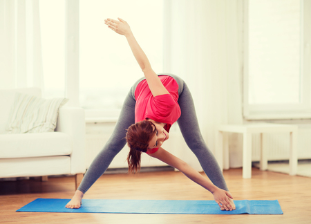 moves: fitness, home and diet concept - smiling teenage girl streching at home Stock Photo