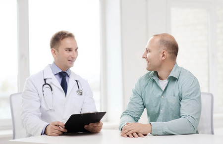doctor consultation: healthcare and medicine concept - smiling doctor with clipboard and patient in hospital Stock Photo