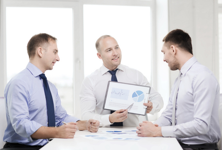 business and office concept - smiling businessman showing others charts in office photo