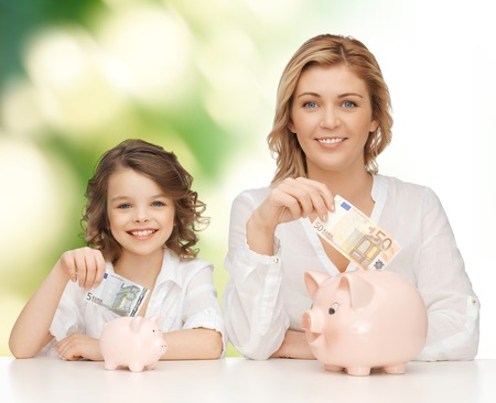 family budget: people, finances, family budget and savings concept - happy mother and daughter with piggy banks and paper money over green background