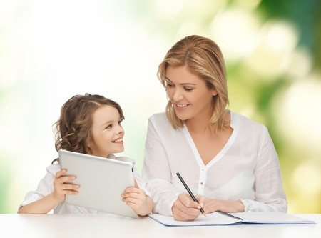 people, family, home education, children and technology concept - happy mother and daughter with tablet pc and notebook over green background Standard-Bild
