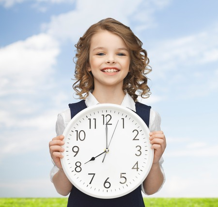 people, time management and children concept - smiling girl holding big clock showing 8 oclock