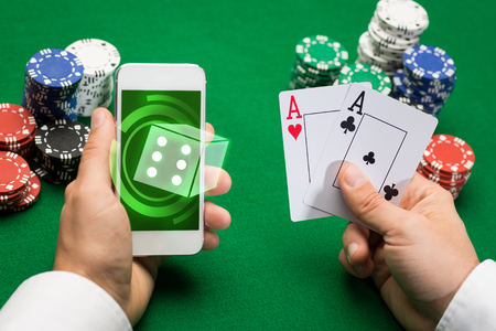 smartphone addiction: casino, online gambling, technology and people concept - close up of poker player with playing cards, smartphone and chips at green casino table