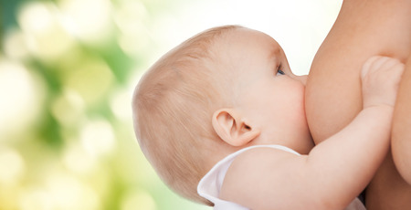 mother milk: motherhood, children, people and care concept - close up of mother breast feeding adorable baby over green background